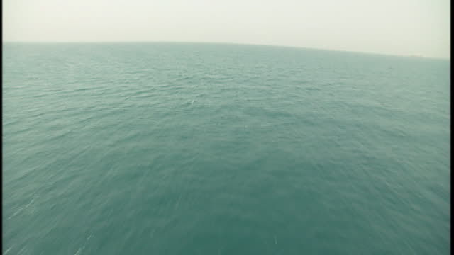 an aerial view reveals a long rock breakwater and a vast expanse of the blue persian gulf. - seascape stock videos & royalty-free footage