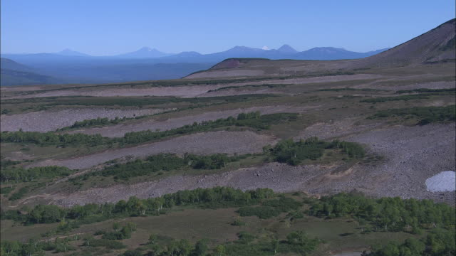 an aerial view reveals patches of woods and rocky soil in russia's kamchatka peninsula. - wilderness stock videos and b-roll footage