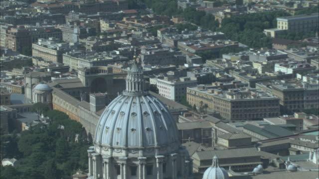 an aerial view reveals saint peter's basilica in vatican city. - stato del vaticano video stock e b–roll