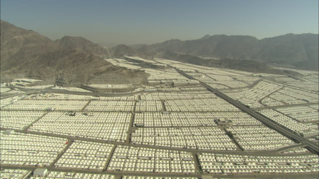 an aerial view reviews a vast area of rows of white tents  in saudi arabia. - hajj stock-videos und b-roll-filmmaterial