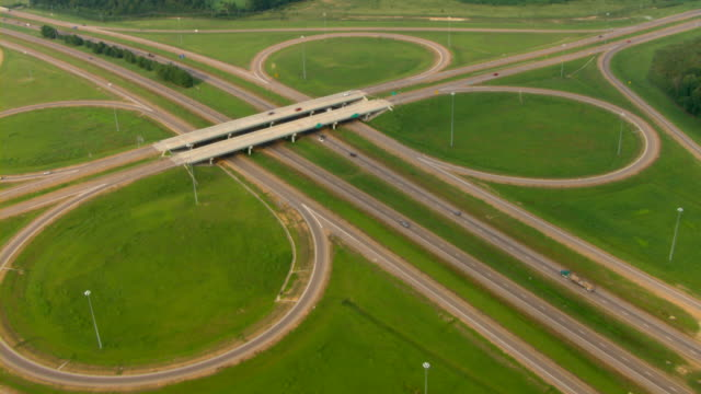 an aerial view shows a cloverleaf traffic pattern along a mississippi highway. - clover leaf shape stock videos and b-roll footage