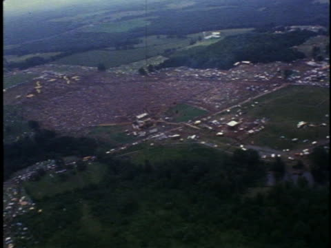 an aerial view shows a mass of parked cars and a field of spectators at the woodstock music festival. - 1969 stock videos & royalty-free footage