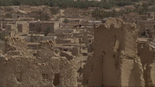 an aerial view shows a vast deserted city with crumbling adobe buildings. - adobe bildbanksvideor och videomaterial från bakom kulisserna