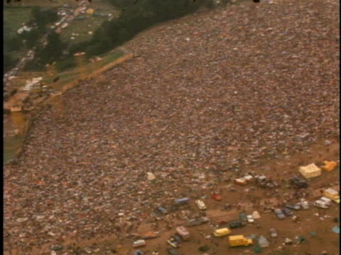 vidéos et rushes de an aerial view shows the thousands of attendees at max yasgur's farm for the woodstock music festival. - 1969