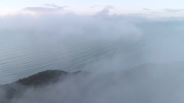 An aerial view through clouds towards the West Coast at Gillespie Beach. New Zealand.