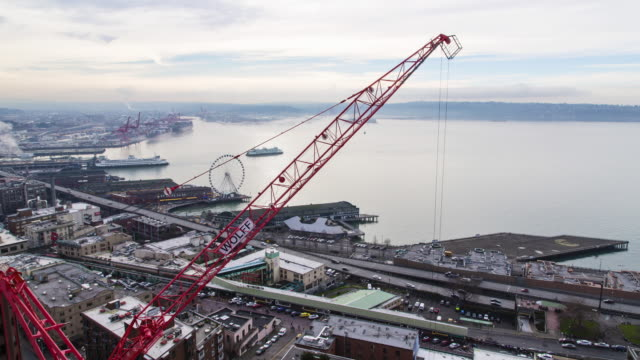 An aerial, winter, daytime time lapse of a construction crane at work with land and sea traffic along the Seattle waterfront in the background