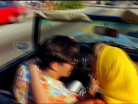 an affectionate young couple enjoys a drive in their convertible through the streets of miami beach, florida. - cabrio stock-videos und b-roll-filmmaterial