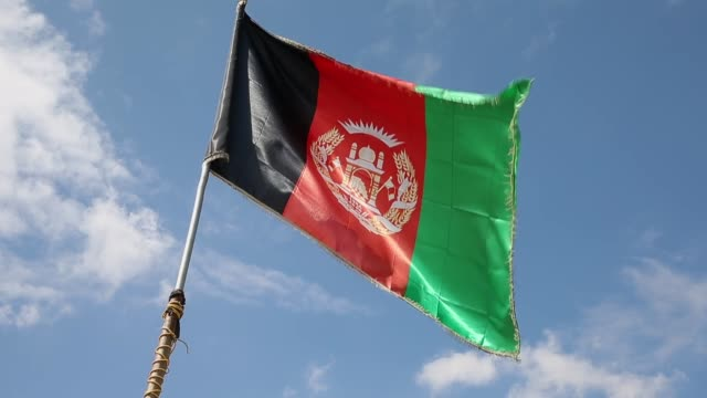 cu an afghan flag flies above and afghan national army outpost near forward operating base shank on march 29 2014 near pule alam afghanistan - 懐中時計点の映像素材/bロール