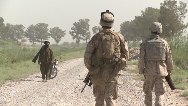 An Afghan man raises his robes, to show he has no weapons, as he approaches U.S. Marines on patrol.