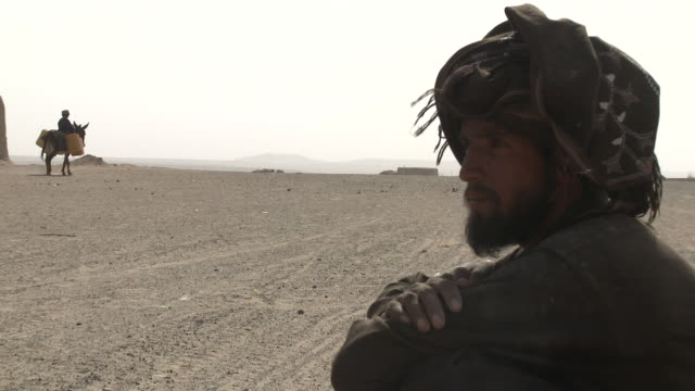 an afghan man squats and watches as a boy rides a laden donkey across a dusty plain. - provinz helmand stock-videos und b-roll-filmmaterial