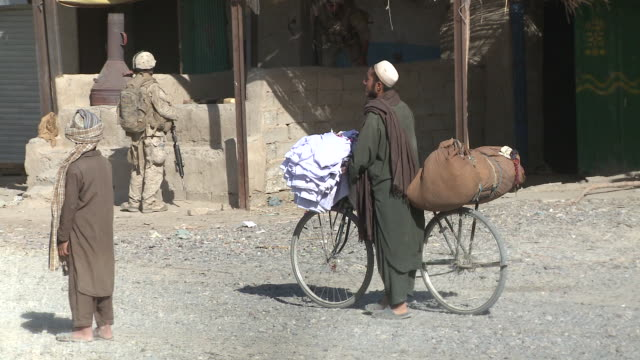 An Afghan man wheels textiles on a bicycle past U.S. Marines in a village.