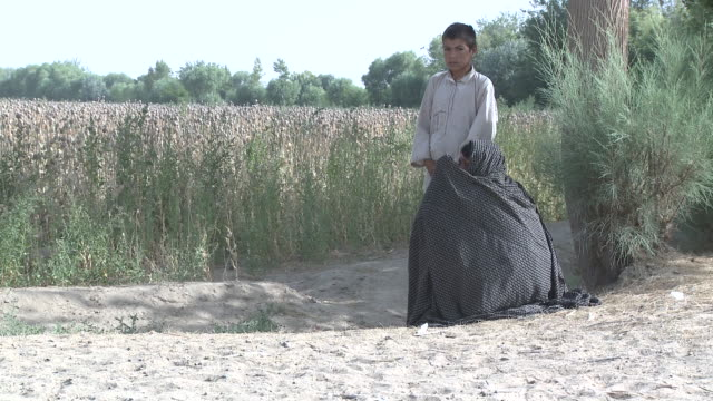 An Afghan woman in a burka squats and hides her face as a U.S. Marine drives past.