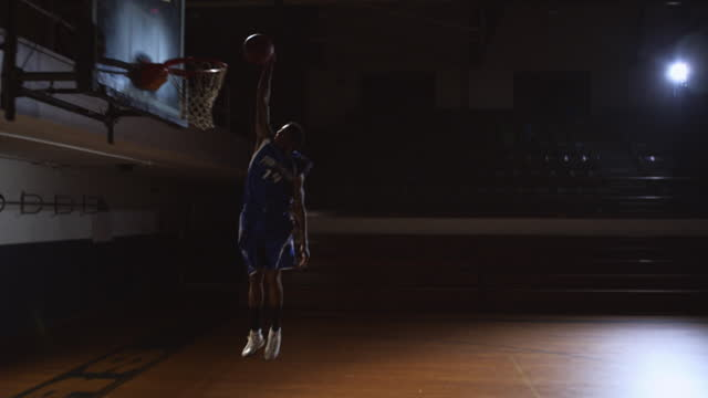 slo mo. an african american athlete in spotlight dribbles down the court and scores a layup. - コート点の映像素材/bロール