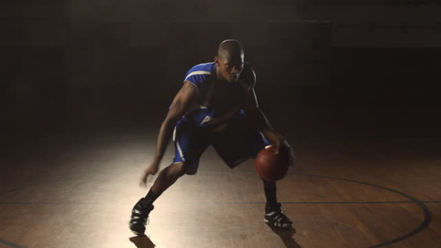 an african american athlete passes the ball from one hand to the other then transitions to intense dribbling techniques. - basketball stock videos and b-roll footage