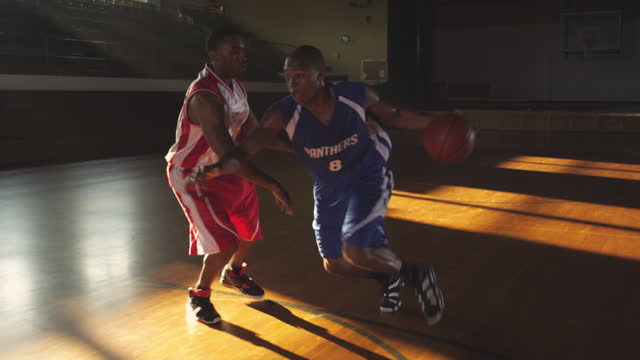 SLO MO. An  African American athlete practices offensive dribbling techniques against another basketball player.