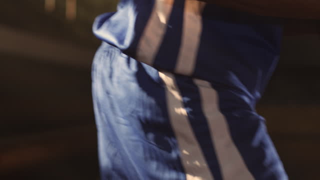 slo mo. an african american athlete sits courtside with a basketball in his hands in an empty gym then rises and walks away. - african american ethnicity stock videos & royalty-free footage