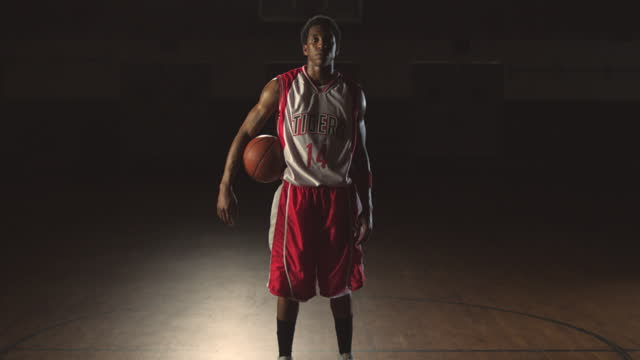 vidéos et rushes de an african american athlete stands resolute with a basketball tucked under his arm in an empty gym. - joueur de basket ball