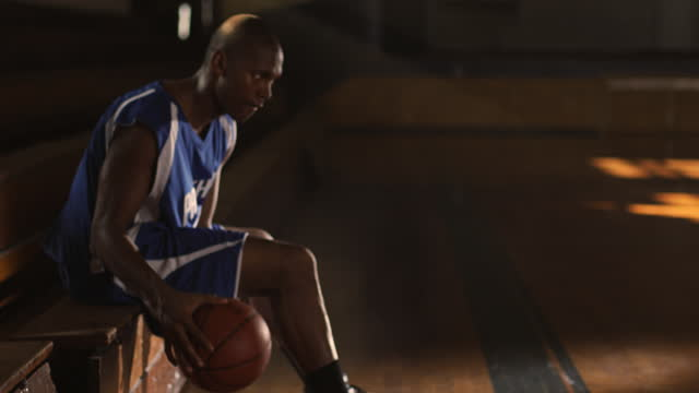 SLO MO. An African American basketball player sits courtside in an empty gym dribbling beneath his legs.