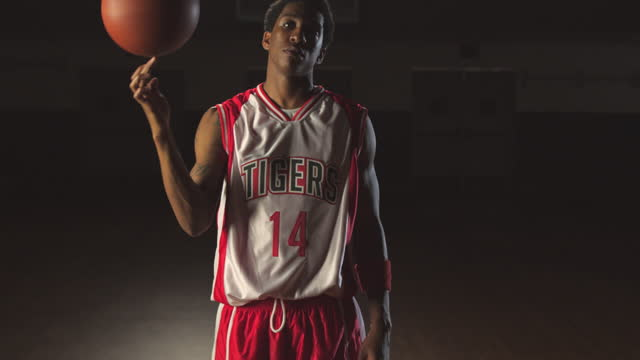A male basketball player shows confidence while spinning the ball on one finger.