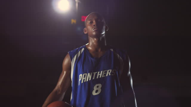vidéos et rushes de an african american basketball player stops dribbling and tucks the ball under his arm as he stares in the camera. - chiffre 8