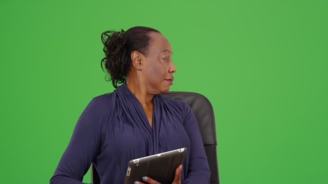 an african american businesswoman holding a tablet on green screen - maestra video stock e b–roll