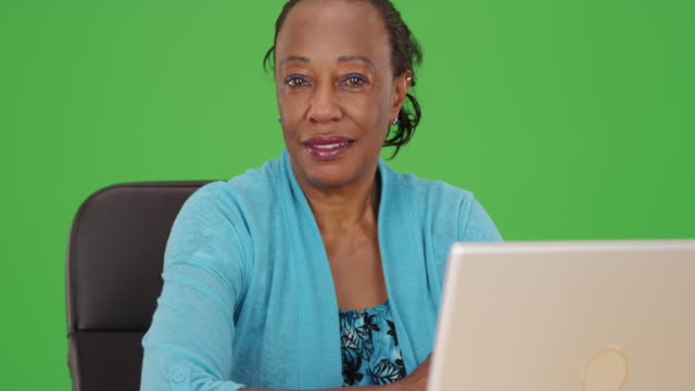 an african american businesswoman poses for a portrait while using her laptop on green screen - maestra video stock e b–roll