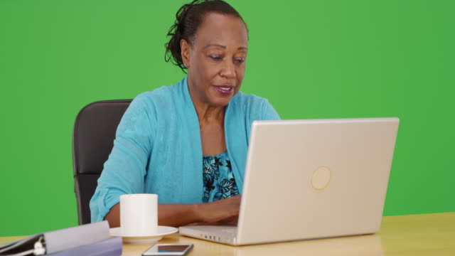 vídeos de stock e filmes b-roll de an african american businesswoman uses her laptop at her desk on green screen - adulto maduro
