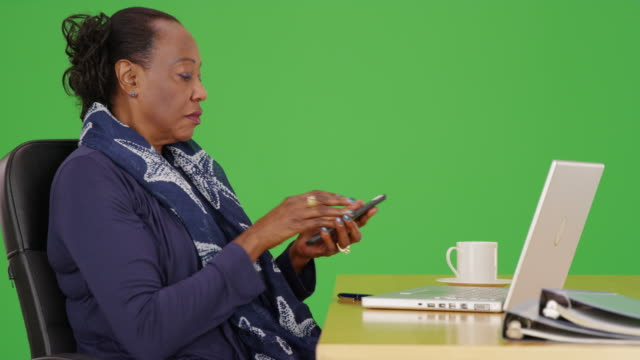 an african american businesswoman uses her mobile phone at her desk on green screen - maestra video stock e b–roll
