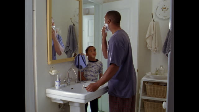 vídeos de stock, filmes e b-roll de an african american man applies shaving cream and shaves while a boy watches. - raspando