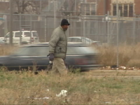 an african american man walking along side the road in michigan. - ポンティアック点の映像素材/bロール