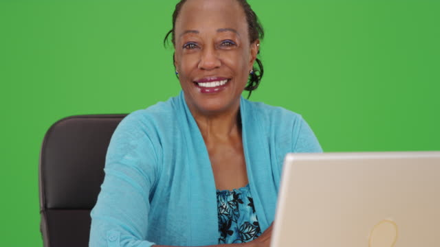 an african american woman happily uses her computer at work on green screen - maestra video stock e b–roll