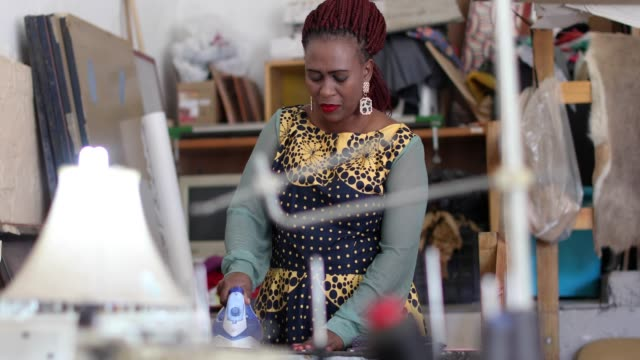 an african woman making face masks in her fashion design studio. - fashion designer stock videos & royalty-free footage