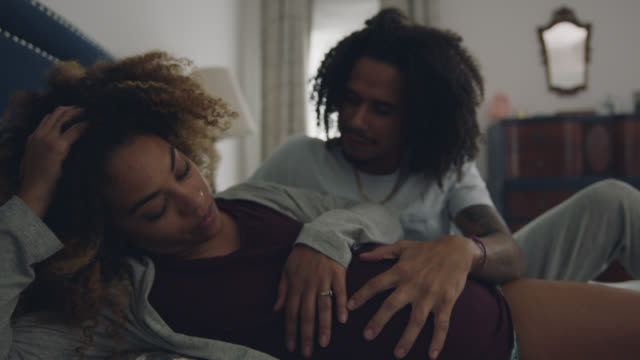 an african-american man rubs the belly of his exhausted girlfriend's pregnant belly - pregnant stock videos & royalty-free footage