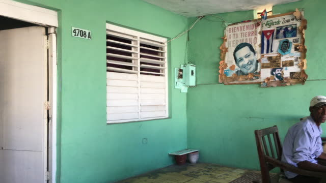an afro caribbean man sits in his house porch with his large dog and chats with people passing by there is a political mural in the wall where the... - cuban culture stock videos & royalty-free footage