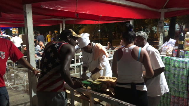 an afrocaribbean man wearing a usa flag shirt speaks to the people in a pulled pork sandwich kiosk although some cubans wear the usa flag when asked... - cuban culture stock videos & royalty-free footage