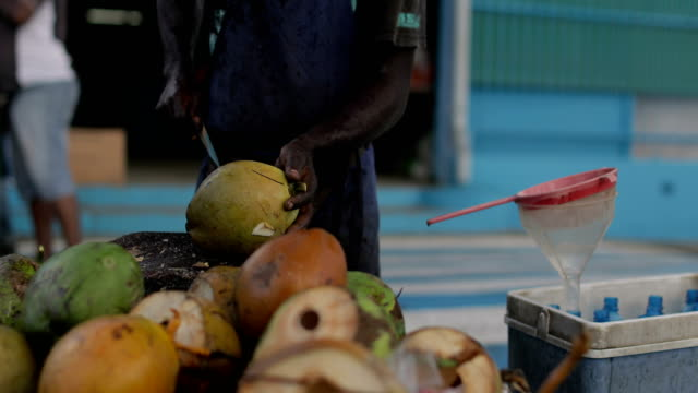 stockvideo's en b-roll-footage met an afro-caribbean market trader sells coconut water and drinking coconuts on a local market in martinique - marktkoopman