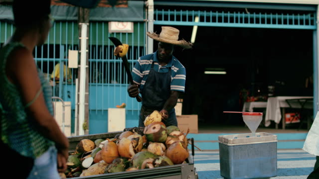 stockvideo's en b-roll-footage met an afro-caribbean market trader sells coconut water and drinking coconuts on a local market in martinique - french overseas territory