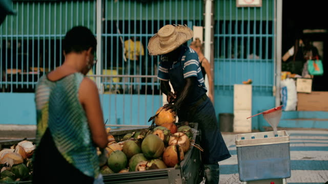 an afro-caribbean market trader sells coconut water and drinking coconuts on a local market in martinique - french overseas territory stock videos & royalty-free footage