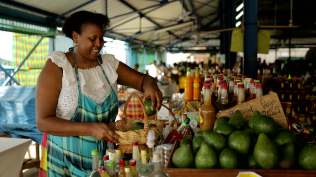 stockvideo's en b-roll-footage met an afro-caribbean market woman sells avocados at a local market in martinique - marktkoopman