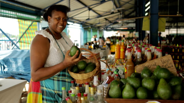 An Afro-Caribbean market woman sells avocados at a local market in Martinique