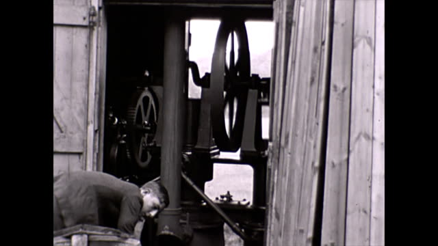an agricultural steam pump being attended to by a young man the piston flywheel and gears can be seen working / water is drawn and pumped out into a... - vattenpump bildbanksvideor och videomaterial från bakom kulisserna