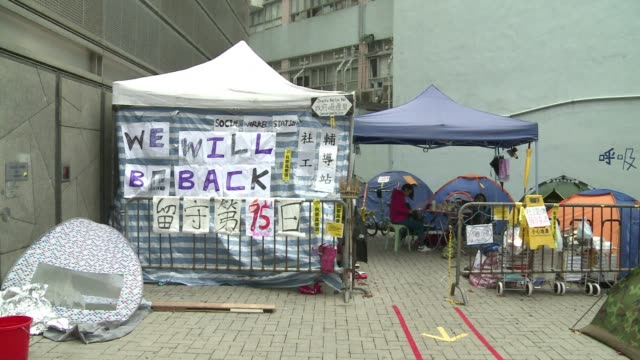 vídeos de stock, filmes e b-roll de an air of tired resignation hangs over hong kongs main pro democracy protest site as demonstrators brace for a police clearance after more than two... - brace
