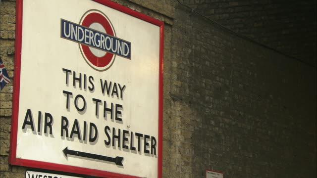an air raid shelter sign hangs on a wall. - air raid stock videos & royalty-free footage