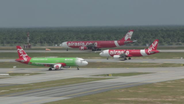An AirAsia Bhd aircraft right prepares to take off as another AirAsia Bhd aircraft taxis on the tarmac at Kuala Lumpur International Airport 2 in...