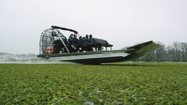 Un hydroglisseur vitesses flottant Salvinia (Fern) dans la rivière Atchafalaya Basin marais dans le sud de la Louisiane sous un ciel couvert