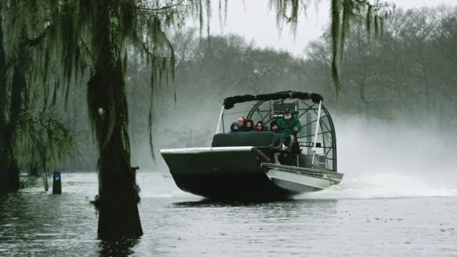 vidéos et rushes de un tour en airboat dans le marais de bassin de rivière atchafalaya dans le sud de la louisiane sous un ciel couvert - louisiane