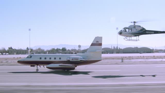 vidéos et rushes de an airborne helicopter follows a private jet speeding down a runway. - piste d'envol