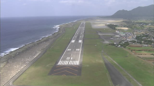 an aircraft approaches the runway of tokunoshima airport on tokunoshima island, japan. - campo d'aviazione video stock e b–roll