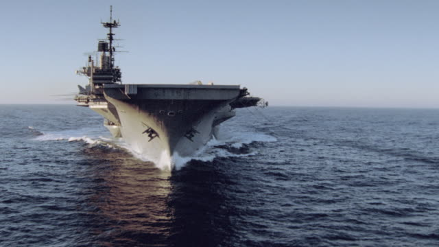 vidéos et rushes de an aircraft carrier cruises slowly through a calm ocean. - aller tranquillement