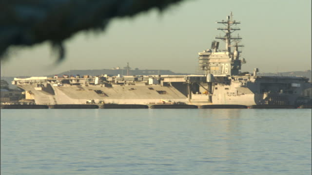 stockvideo's en b-roll-footage met an aircraft carrier floats in a harbor in san diego. - san diego
